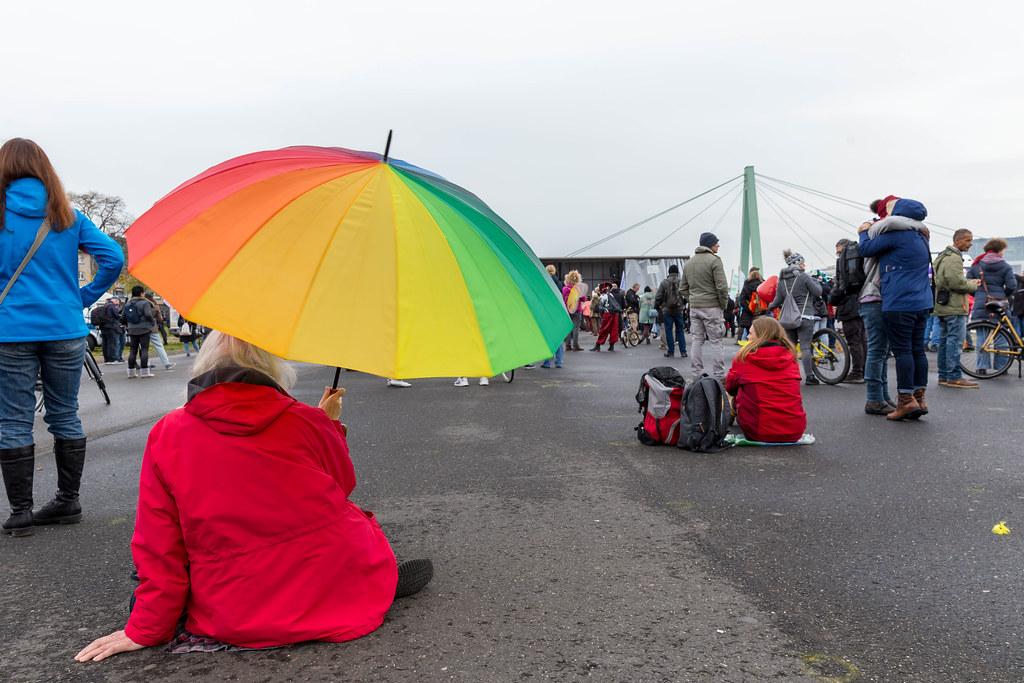 Deutzer Werft, Köln: Frau mit Regenbogenschirm und rote Jacke bei Demo gegen Corona-Regeln