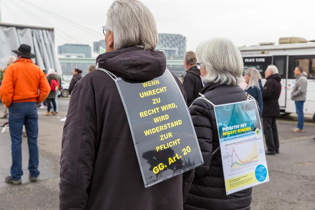 Zwei Teilnehmer an der Anti-Corona-Demo in Köln mit Schildern gegen die Corona-Maßnahmen