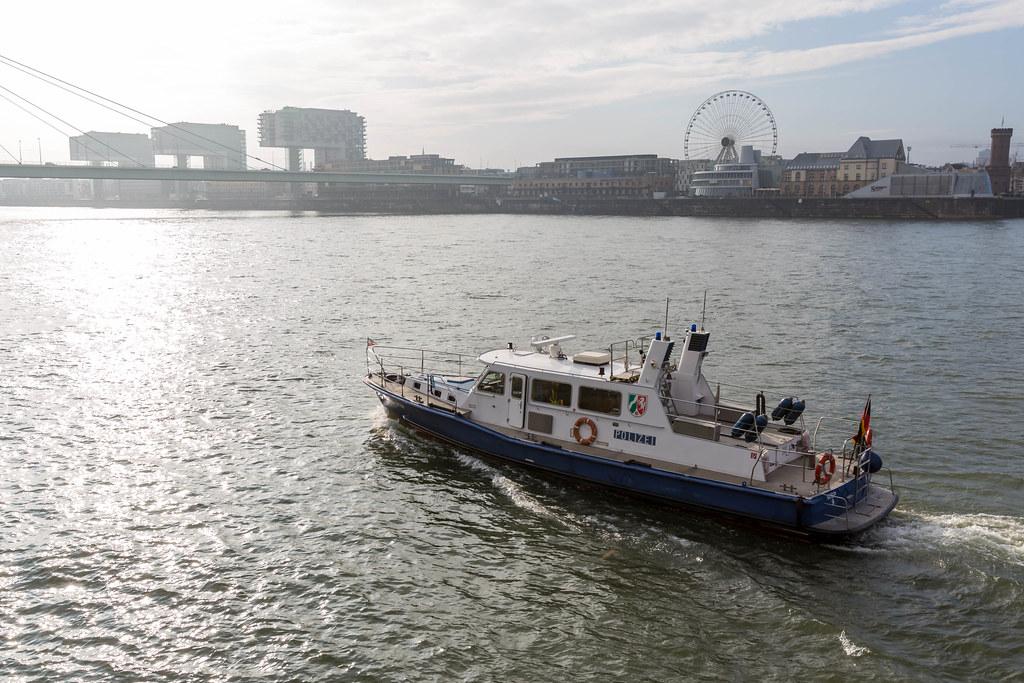 Ein Polizeiboot am Rhein in Köln mit Riesenrad und Kranhäusern im Hintergrund
