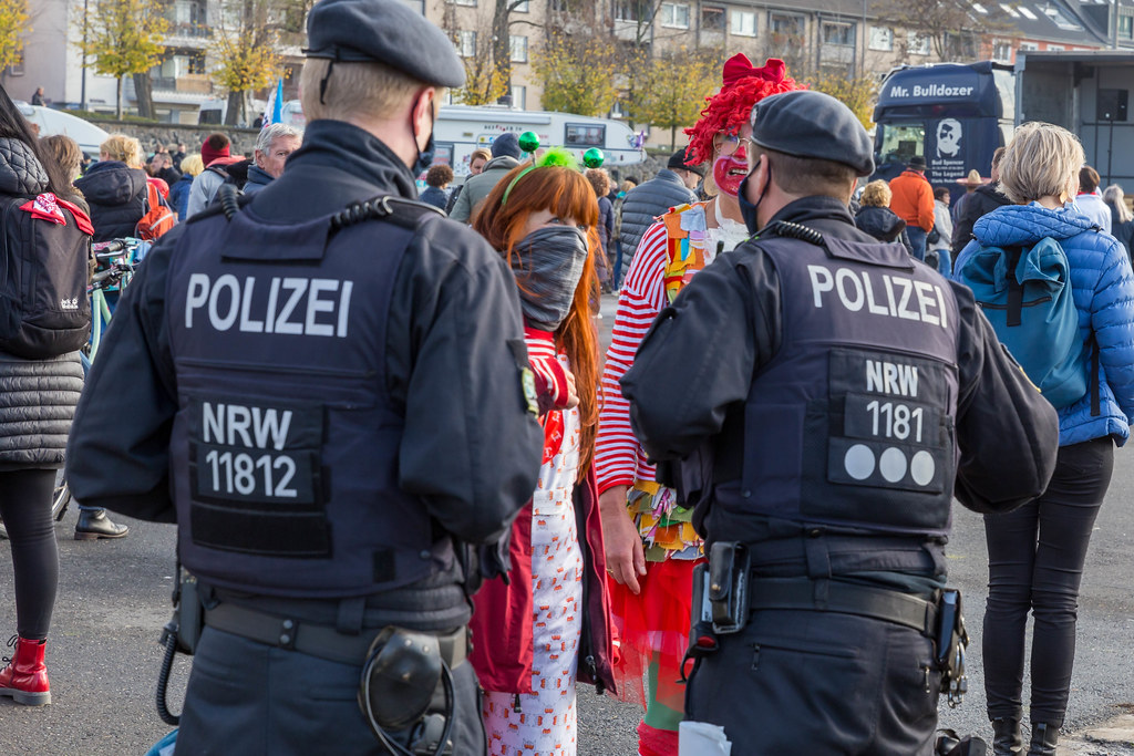 Two women in traditional Cologne red-white carnival costumes talk to the police at coronavirus protest