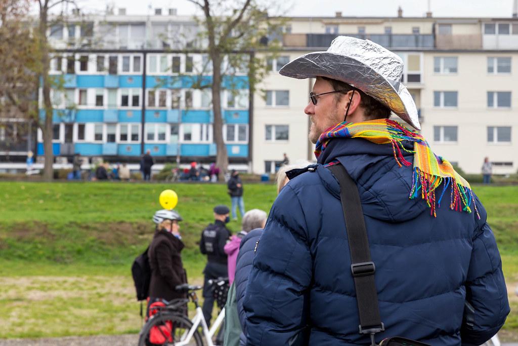 Mann mit Regenbogen-Schal und Aluhut und ohne Mundschutz bei der Anti-Corona-Demo in Köln
