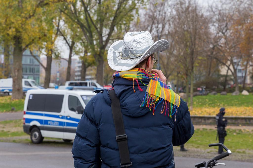 Mann mit Aluhut in Cowboy-Stil ohne Maske mit Polizeifahrzeug im Hintergrund. Anti-Corona-Demo