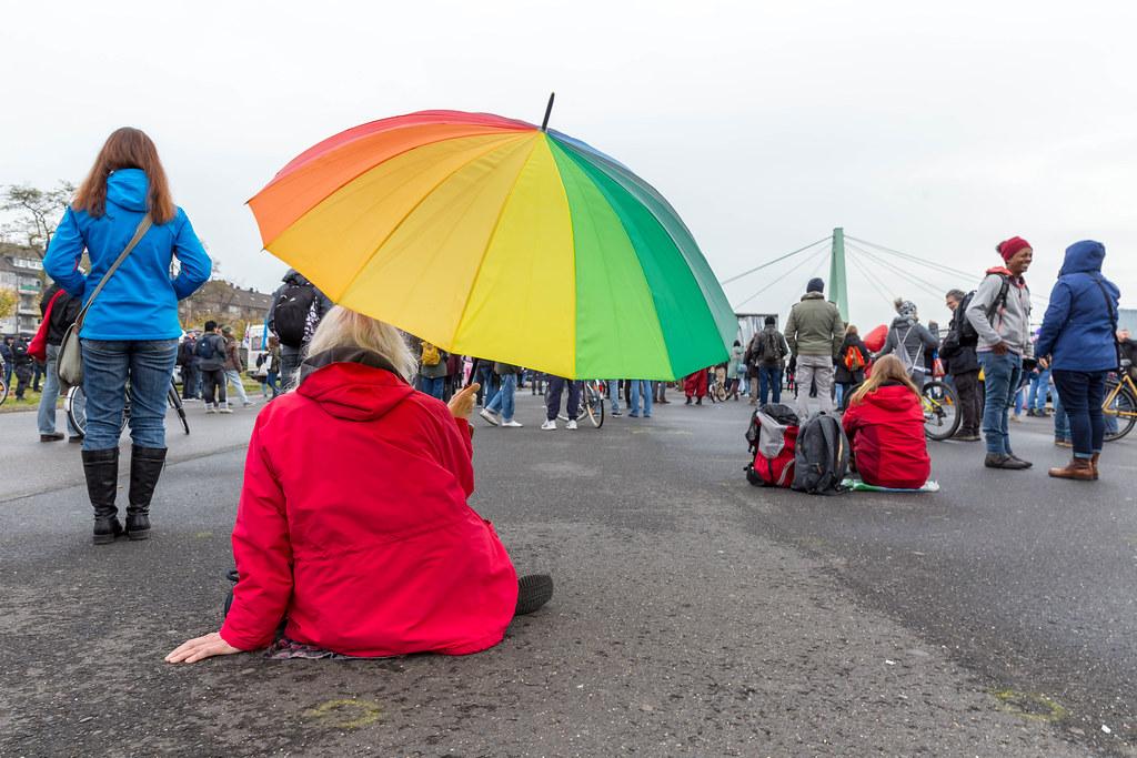 Regenbogen gegen Corona: Frau mit Regenbogen-schirm als Symbol für Frieden bei Anti-Corona-Demo
