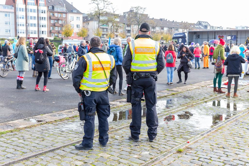 Zwei Beamte vom Ordnungsamt überwachen die Demo gegen die Corona-Maßnahmen in Köln