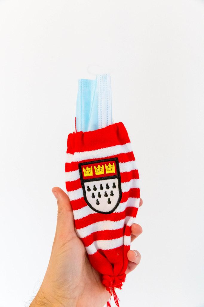 Hand hält einen Kölschglashalter mit dem Kölner Wappen in rot/weiß mit Mundschutz statt Glas