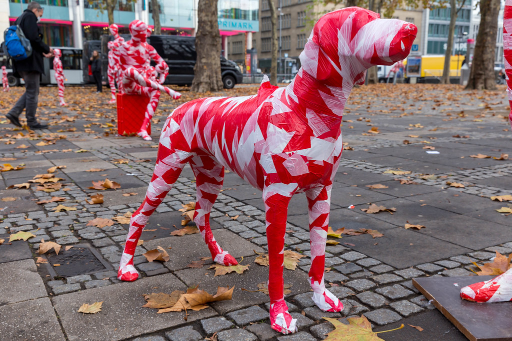 Eine Hundfigur wrapped in red-white barrier tape as part of the Covid-19 art installation