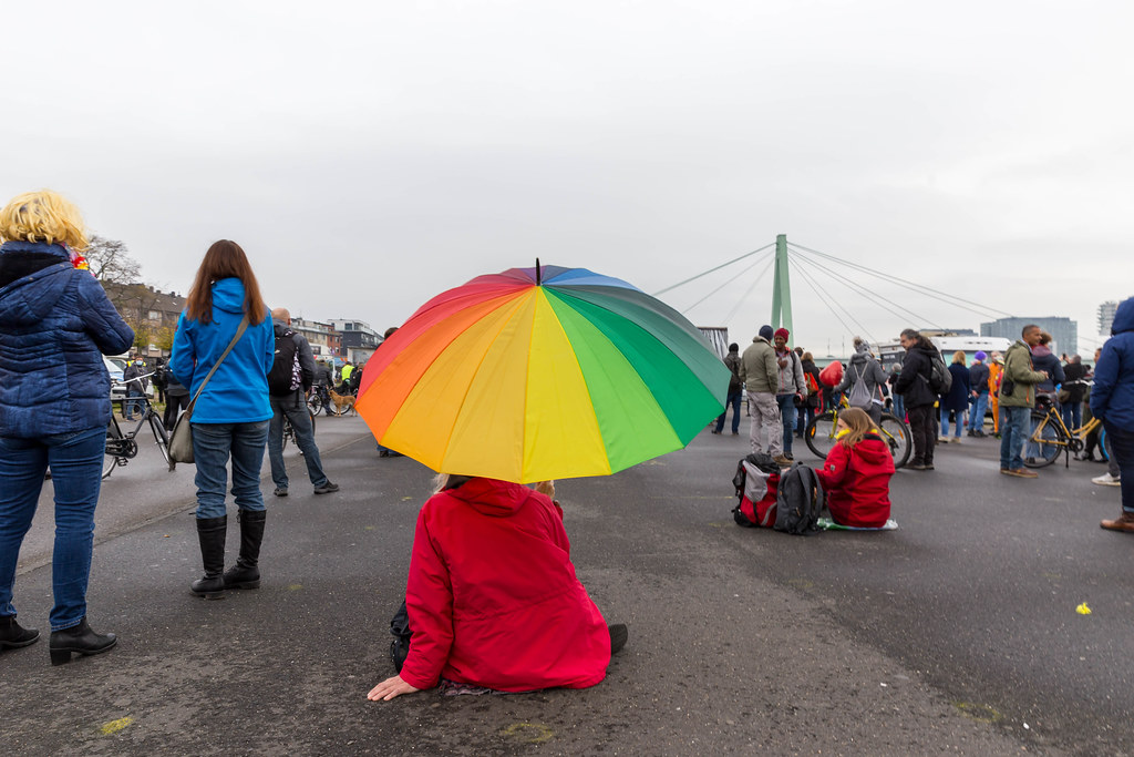 Deutzer Werft, Cologne: woman with rainbow umbrella, red jacket at demo against Covid-19 rules