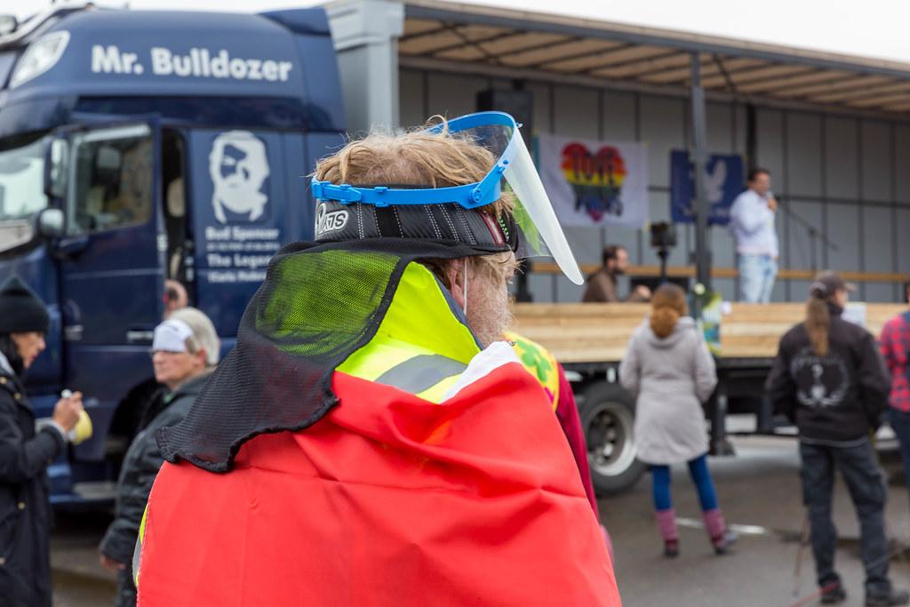 Anti-Corona-Demo in Köln: rauchender Mann trägt Gesichtsvisier, Warnschutzjacke und roten Mantel