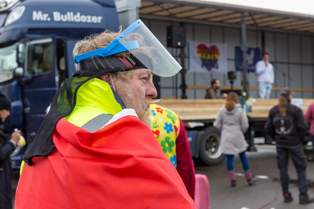Coronavirus protest in Germany: smoking man with plastic face shield, red cape and high-visibility jacket