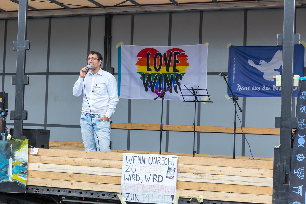 Anti-Covid protestor without face mask holds speech from truck with rainbow heart and motto