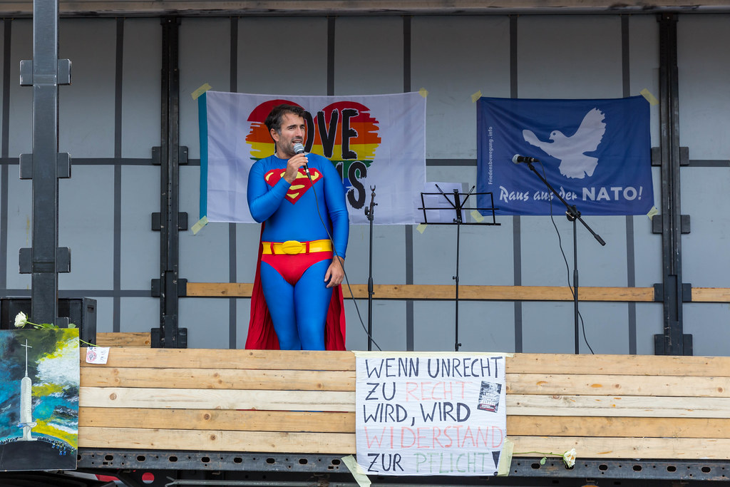 Man in Superman costume holds a speech from the stage of the anti-Covid demo in Cologne