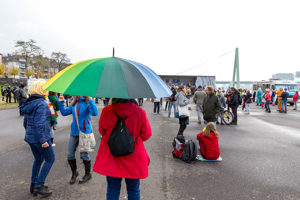 Woman with rainbow umbrella as symbol of peace at rally against anti-Covid measures in Cologne