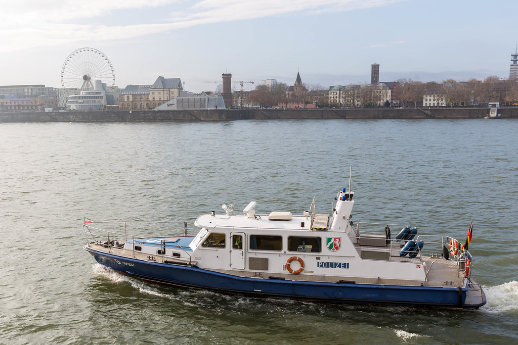 Cologne, Germany: police motorboat patrolling the Rhine with ferris wheel in the background