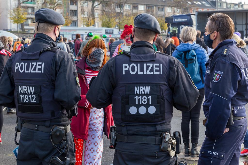 Polizisten reden mit einer Frau mit Halstuch als Mundschutz, in traditionellen Farben von Köln verkleidet