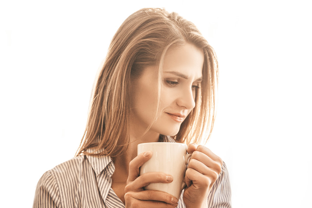 Beautiful woman with cup of tea standing near window