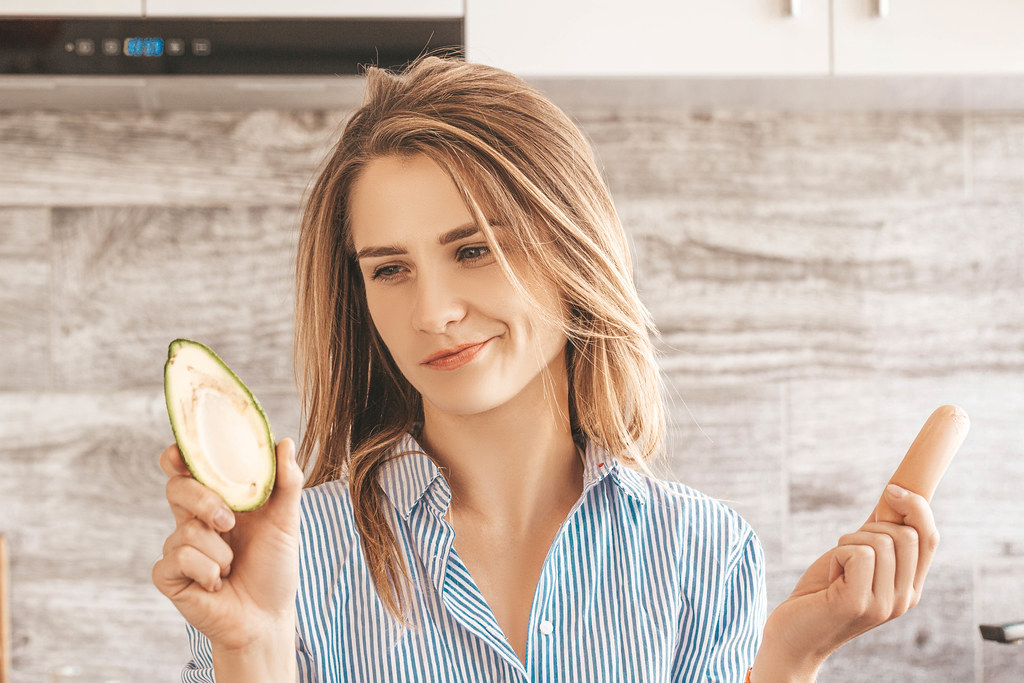 Beautiful girl in the kitchen with a sausage and avocado in her hands. The concept of choosing between healthy and unhealthy food