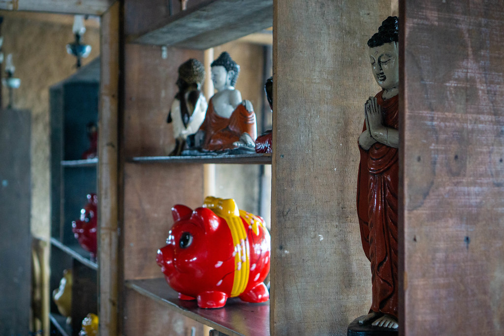 Different Buddha Statues such as Lady Buddha and Piggy Banks for Good Luck in a Shelf