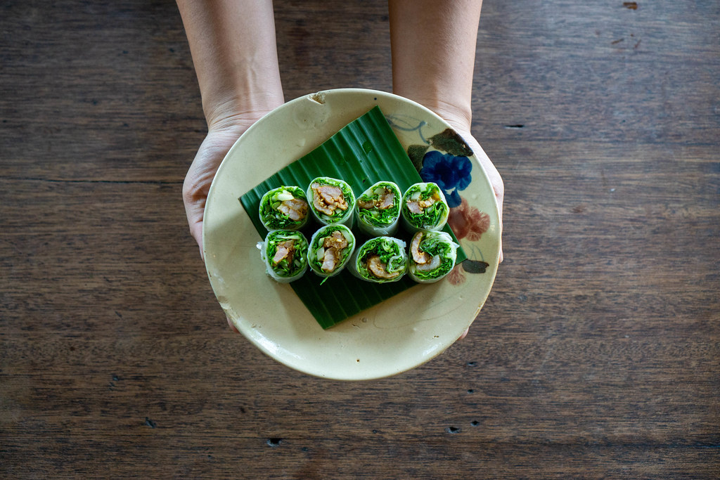 Top View Food Photo of Person holding a Plate of Vietnamese Summer Rolls with Grilled Meat and fresh Herbs