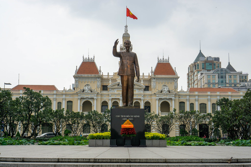 Statue of Ho Chi Minh with People's Committee of Ho Chi Minh City with waving Vietnam Flag in the Background