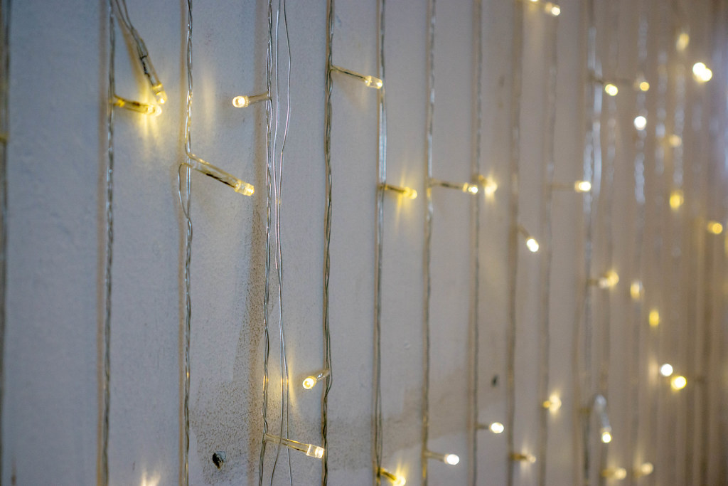 Bokeh Photo of String Lights hanging down a White Wall in a Cafe