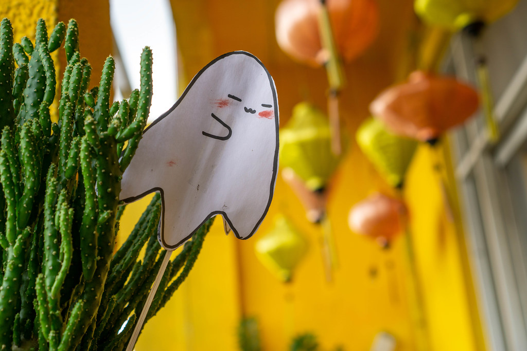 Bokeh Photo of Paper Ghost Halloween Decorations in a Mini Cactus with Hanging Lanterns in the Background