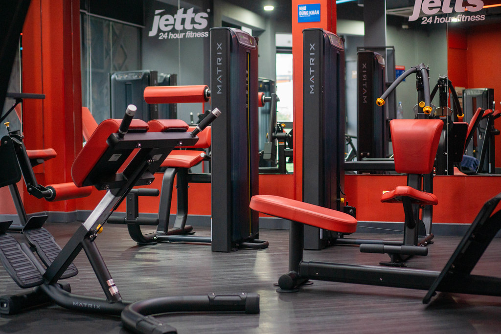 Different Exercise Machines and Benches with a large Mirror in a Gym