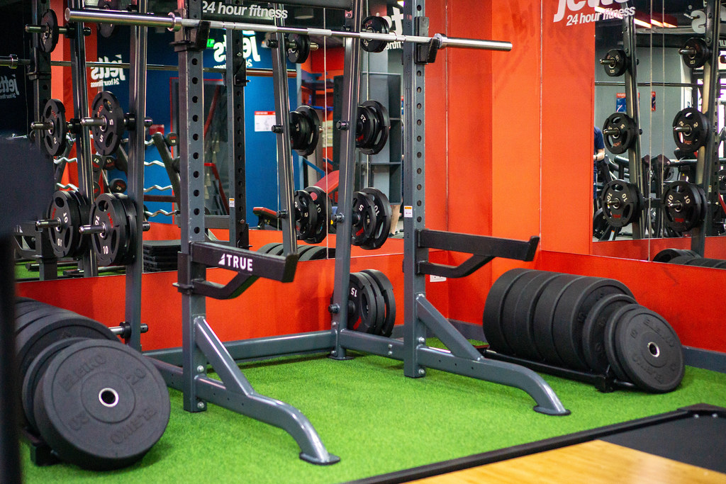 Multi-Purpose Squat Rack with Barbell and several Weight Plates in front of a Mirror in a Gym