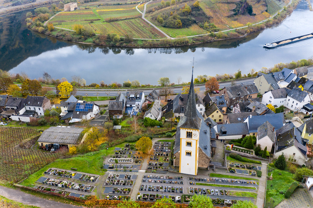 Drone Photo of Saint Lawrence Church with Car Parking Space and Residential Houses with River Moselle in Bremm, Germany