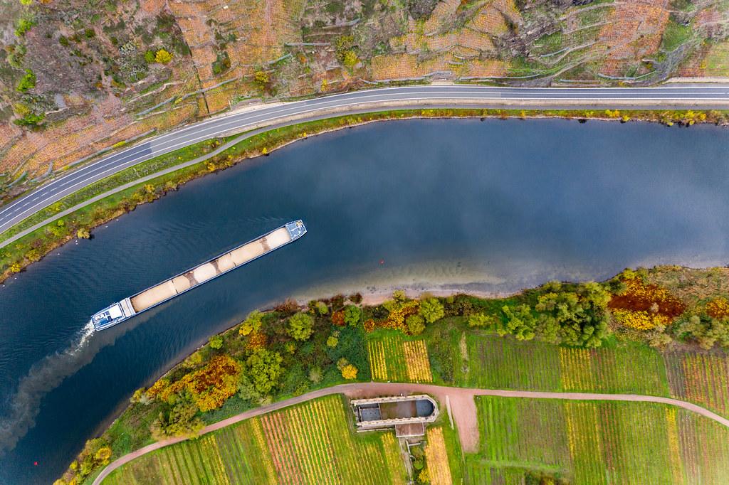 Drohnenaufnahme in der Vogelperspektive von einem Frachtschiff mit Sand auf dem Fluss Mosel mit Klosterruine Stuben und Weinbauflächen am Randhöhenzug Calmont