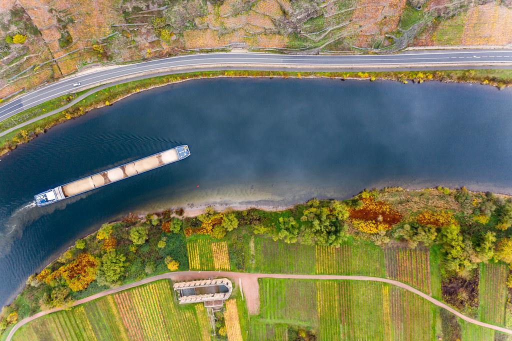 Ein mit Sand beladenes Frachtschiff fährt auf der Mosel vorbei an Kloster Stuben und Weinbergen am Berg Calmont in Bremm, Deutschland Luftaufnahme