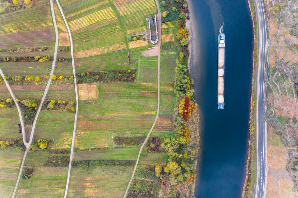 Bird View Drone Photo of Large Cargo Vessel loaded with Sand on River Moselle with Vineyards, Agriculture and Historical Landmark Kloster Ruine Stuben in Bremm, Germany