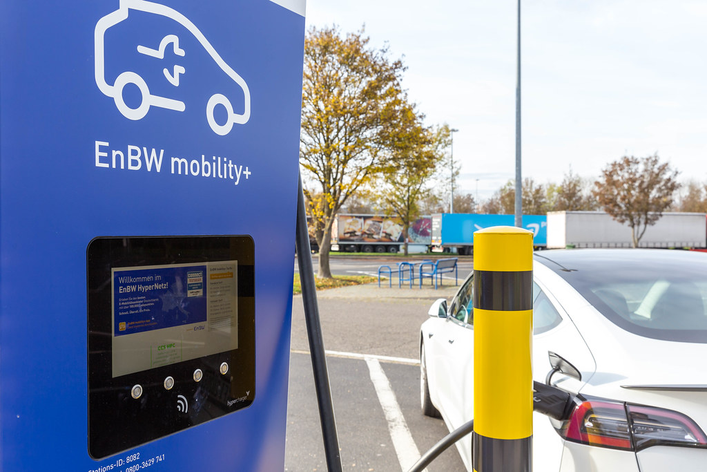 A Car is charging on a modern EnBW mobility+ Electric Vehicle Charging Station at a Rest Stop in Rhineland-Palatinate, Germany