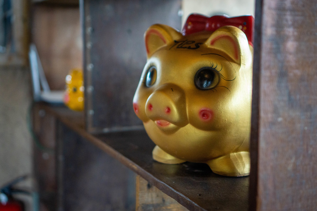 Golden Piggy Bank with Big Eyes and Red Bow Tie in a Wooden Shelf as Decoration in a Restaurant in Vietnam
