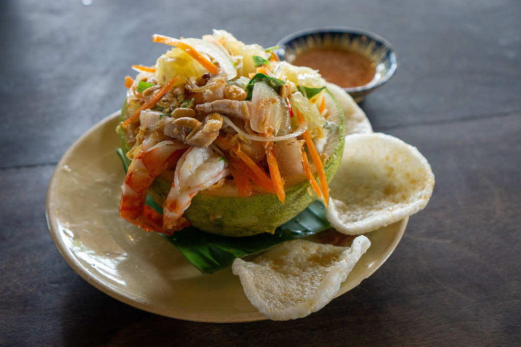 Close Up Food Photo of Pomelo Salad with Shrimps, Carrots, Peanuts, Pork, Shrimp Chips and Fish Sauce with Chili in a Vietnamese Restaurant