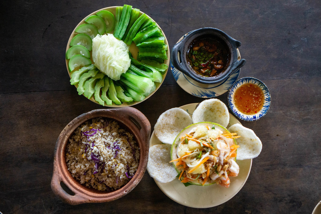 Pomelo Salad with Shrimp Chips, Fried Rice with Fish and Cooked Vegetables with Stew Pork Dip on a Wooden Table from above