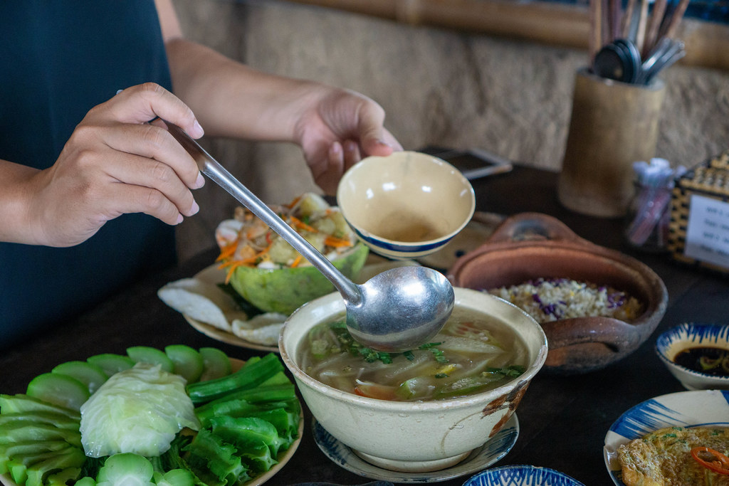 Person is using a Ladle to get Sour Soup with many different Dishes on the Table in a Restaurant in Saigon, Vietnam