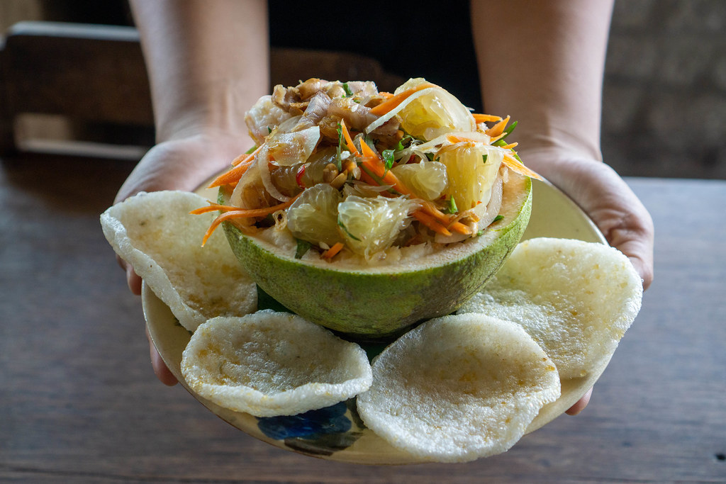Close Up Food Photo of Person holding Plate of Pomelo Salad with Peanuts, Shrimps, Carrots and Shrimp Chips