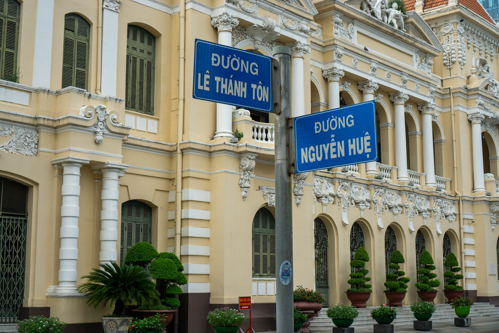 Street Signs of Intersection of Nguyen Hue and Le Thanh Ton Street with People's Committee of Ho Chi Minh City, Vietnam in the Background
