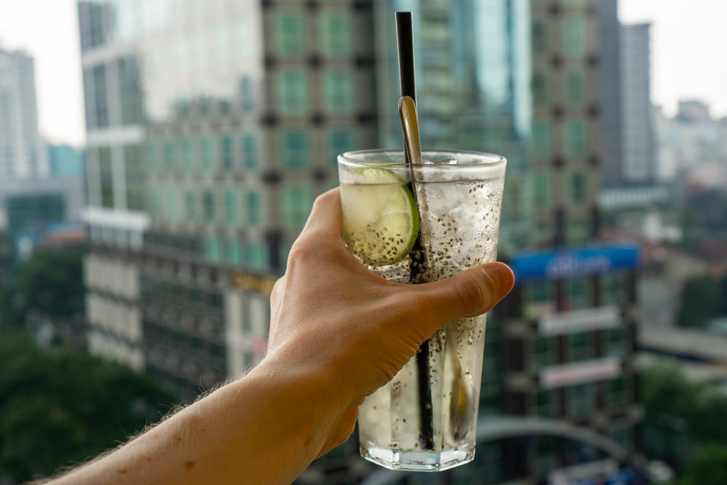 Bokeh Photo of Person holding a Glass of Lemonade with Lime, Chia Seeds and Aloe Vera