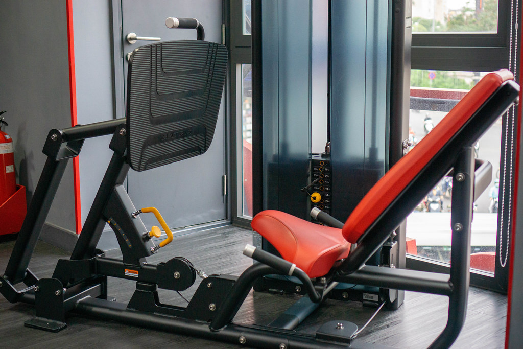 Adjustable Leg Press Machine with Incline Seat in a Gym Room