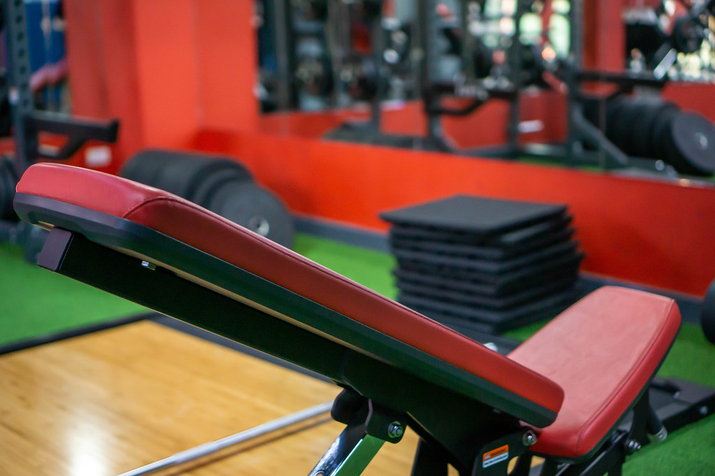 Bokeh Photo of Adjustable Gym Bench with Different Exercise Equipment in a Fitness Center