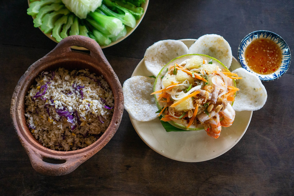 Top View Food Photo of Cooked Vegetables, Fish Fried Rice in Clay Pot, Pomelo Salad with Shrimp Chips, Shrimps and Peanuts in a Vietnamese Restaurant