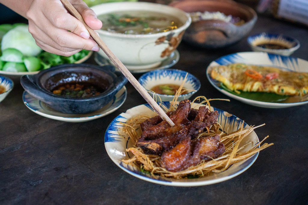 Person is using Wooden Chopsticks to pick Food from different Plates in a Vietnamese Restaurant