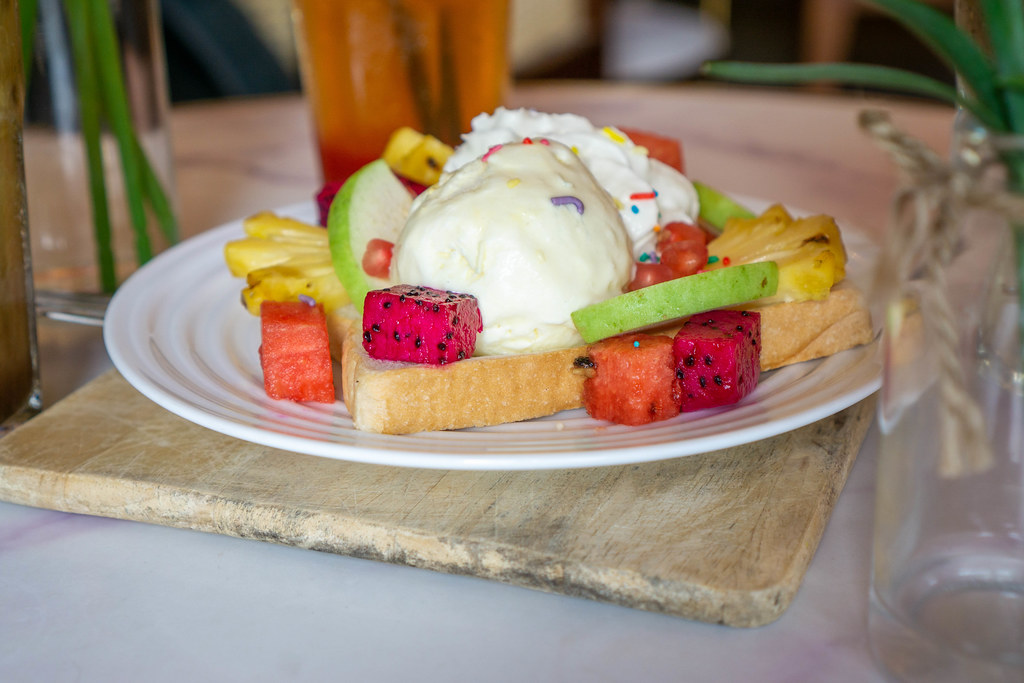Food Photo of Toast with Vanilla Ice Cream and Fruits such as Dragon Fruit, Pineapple, Watermelon and Guava on a White Plate