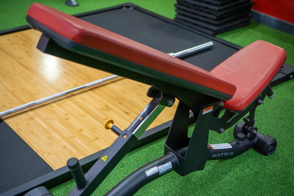 Verstellbare Hantelbank mit Langhantel und anderen Fitnesszubehör im Hintergrund in einem Fitnessstudio