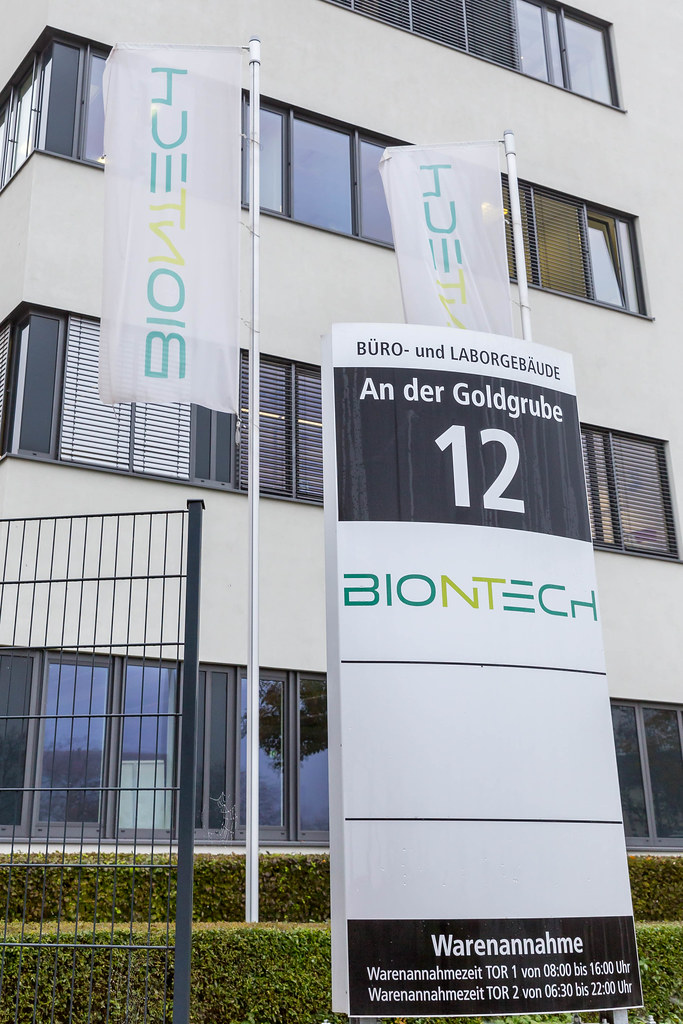 BioNTech Information Signboard with Address An der Goldgrube 12 showing Opening Hours of Acceptance of Goods with BioNTech Flags and Building in the Background