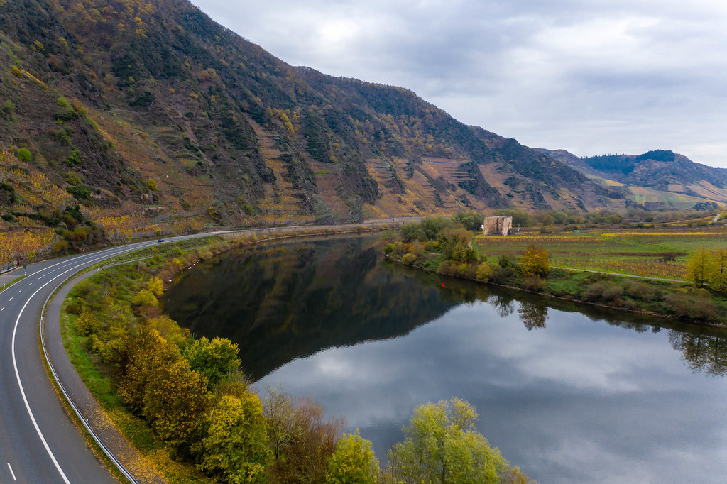 Luftaufnahme von der Bundesstraße B49 entlang der Mosel mit im Fluss reflektierendem Randhöhenzug Calmont in Bremm, Deutschland
