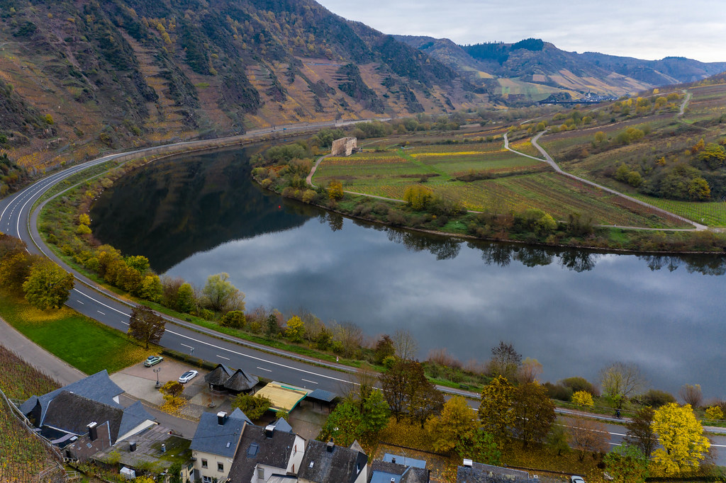 Aerial View of Federal Road B49 along River Moselle with Residential Buidlings and Hill Calmont Reflection in the River in Bremm, Germany