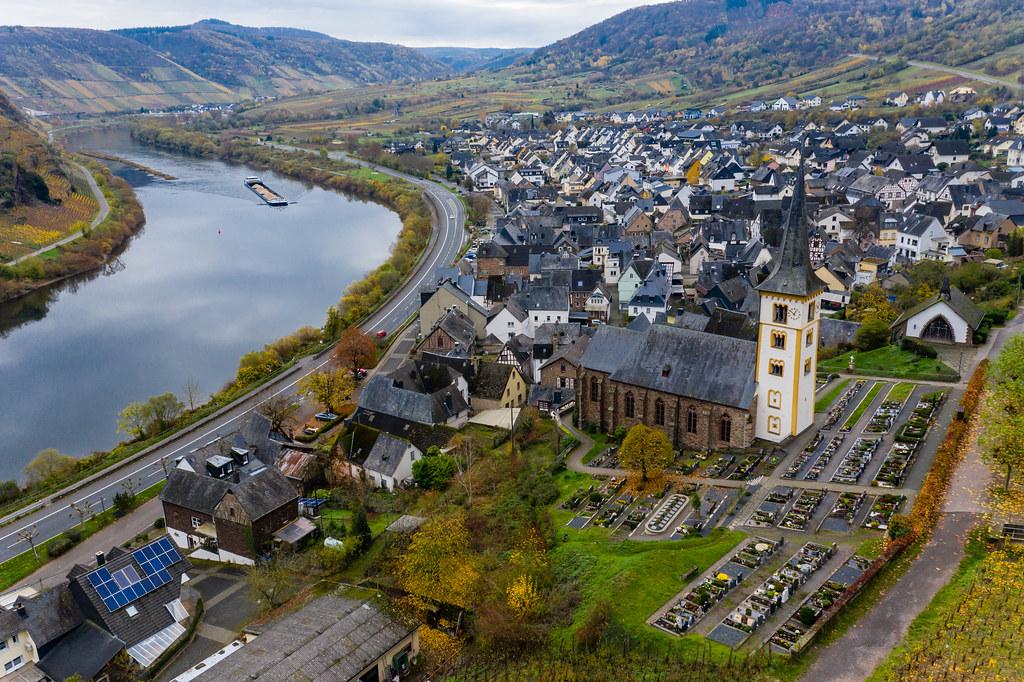 Luftaufnahme der Ortsgemeinde Bremm im Landkreis Cochem-Zell in Rheinland-Pfalz mit Wohngebäude, St. Laurentius-Kirche, dem Fluss Mosel und Bundesstraße B49