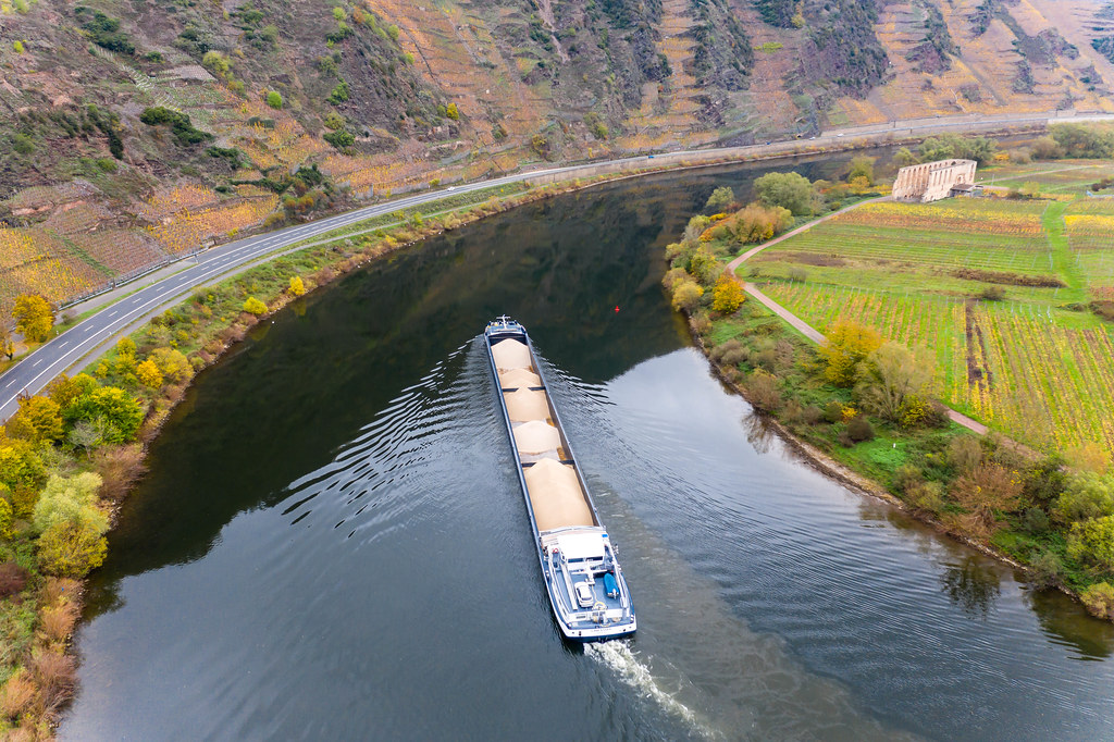 Cargo Ship Loaded with Sand on River Moselle along Highway B49 towards Historical Landmark Kloster Ruine Stuben in Bremm, Germany